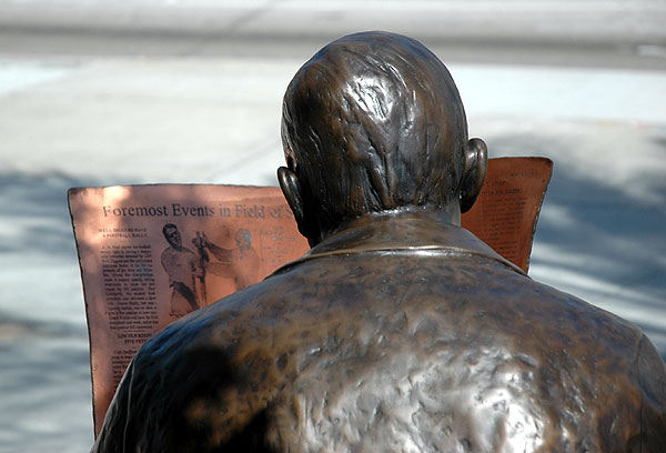 A bronze Harry Culver reads the paper out front -